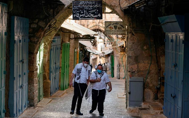 Ultra-Orthodox Jews walk an empty street lined with closed shops on their way to the synagogue for the Rosh Hashana (Jewish New Year) prayers in Jerusalem's old city, amid a second nationwide lockdown in Israel due to a spike in cases - AFP