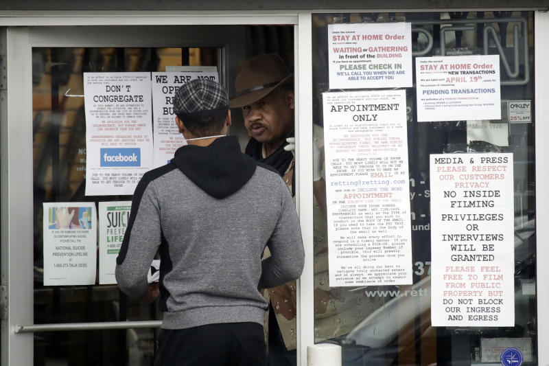 """CORRECTS TO CULVER CITY, INSTEAD OF LOS ANGELES An employee answers questions at the entrance to a gun shop Tuesday, March 24, 2020, in Culver City, Calif. Los Angeles County Sheriff Alex Villanueva said he would like to see gun shops shut down. """"We will be closing them, they are not an essential function,"""" Villanueva said. Adding guns to households where more people are at home during a crisis increases the risk that someone will be shot, he said. (AP Photo/Marcio Jose Sanchez)"""