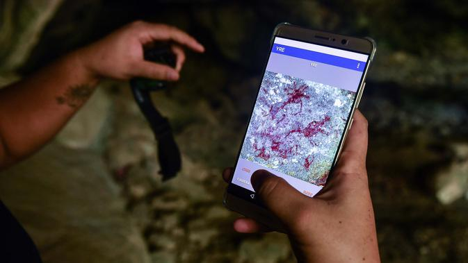 Seorang arkeolog dari Departemen Seni Rupa di Ratchaburi menggunakan aplikasi di ponsel untuk melihat lukisan gua yang baru ditemukan di taman nasional Khao Sam Roi Yot di pesisir provinsi Prachuap Kiri Khan (10/9/2020). (AFP/Lillian Suwanrumpha)