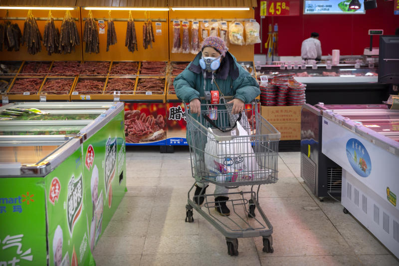 """A woman wears a face mask as she shops at a grocery store in Beijing, Saturday, Feb. 1, 2020. China's death toll from a new virus rose to 259 on Saturday and a World Health Organization official said other governments need to prepare for""""domestic outbreak control"""" if the disease spreads in their countries. (AP Photo/Mark Schiefelbein)"""