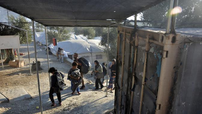 Migran berjalan di kamp pengungsi Moria saat terjadi kebakaran di pulau Lesbos di timur laut Aegean, Yunani, Rabu (9/9/2020). Otoritas kesehatan sebelumnya mengonfirmasi terdapat 35 kasus positif Covid-19 di kamp tersebut setelah melakukan pengujian sampel Covid-19 . (AP Photo/Panagiotis Balaskas)