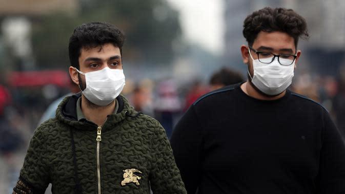 Dua pria mengenakan masker di sebuah jalan di Baghdad, Irak, (25/2/2020). Irak mengumumkan empat kasus baru COVID-19 di Provinsi Kirkuk, wilayah utara, pada Selasa (25/2), sehingga total pasien terinfeksi di negara itu bertambah menjadi lima orang. (Xinhua/Khalil Dawood)