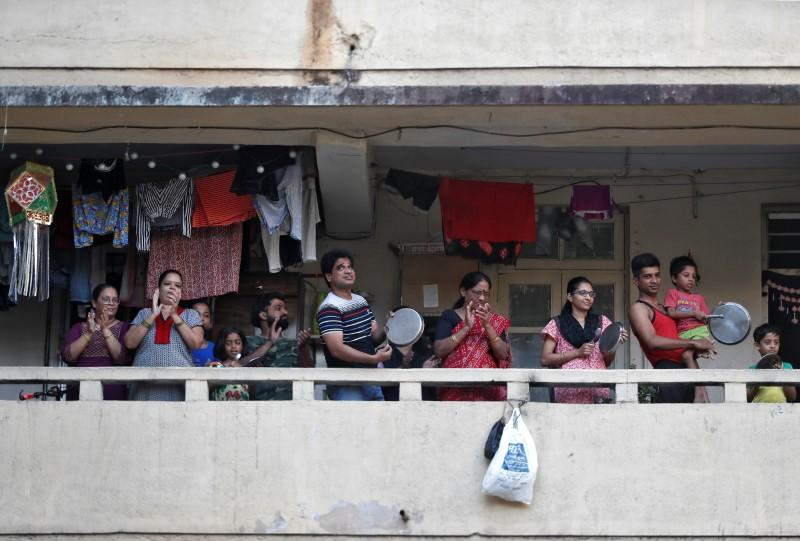 Residents clap and bang utensils from their balconies to cheer for emergency personnel and sanitation workers who are on the frontlines in the fight against coronavirus, in Mumbai