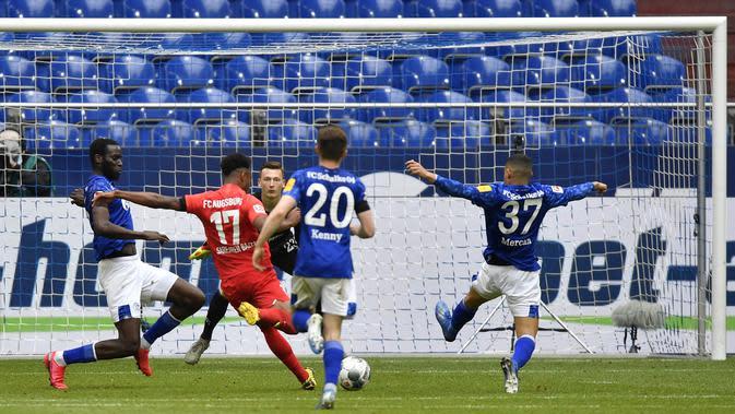 Pemain Augsburg, Noah Saranren Bazee, mencetak gol ke gawang Schalke 04 pada laga Bundesliga di Veltins-Arena, Minggu (24/5/2020). Augsburg menang dengan skor 3-0 atas Schalke 04. (AP/Martin Meissner)