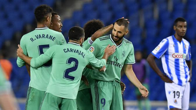 Para pemain Real Madrid merayakan gol yang dicetak oleh Karim Benzema ke gawang Real Sociedad pada laga La Liga di Reale Seguros Stadium, Minggu (21/6/2020). Real Madrid menang 2-1 atas Real Sociedad. (AP Photo/Alvaro Barrientos)