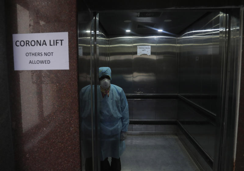 A lift operator stands inside a dedicated lift for people suspected to be infected with the new coronavirus at the Government Gandhi Hospital in Hyderabad, India, March 2, 2020. (AP Photo/Mahesh Kumar A.)