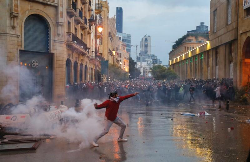 A demonstrator throws a tear gas canister during a protest against a ruling elite accused of steering Lebanon towards economic crisis in Beirut