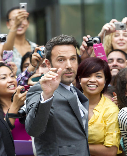 """Actor and director Ben Affleck poses for a photograph with fans at the gala for the new movie """"Argo"""" during the 37th annual Toronto International Film Festival in Toronto on Friday, Sept. 7, 2012. (AP Photo/The Canadian Press, Nathan Denette)"""