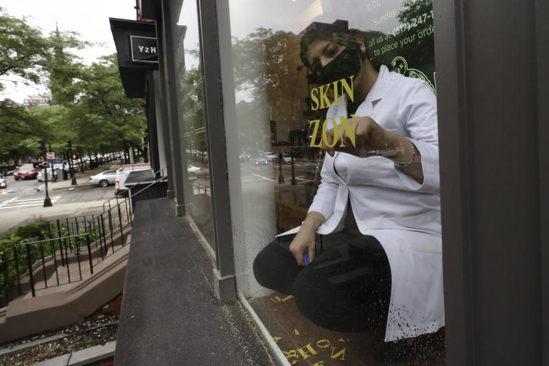 FILE - In this June 11, 2020, file photo a worker removes signage from a storefront window in Boston.  The Trump administration does not have to issue an emergency rule requiring employers to protect workers from the coronavirus, a federal appeals court ruled Thursday, June 11. (AP Photo/Steven Senne, File)