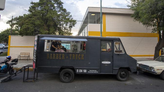 Gerardo (kiri) memangkas rambut pelanggan dalam salon rambut keliling miliknya di Mexico City, Meksiko, 6 Agustus 2020. Gerardo mengubah sebuah mobil van menjadi salon rambut keliling yang menawarkan jasa pangkas rambut kepada warga Mexico City di tengah pandemi COVID-19. (Xinhua/Ricardo Flores)