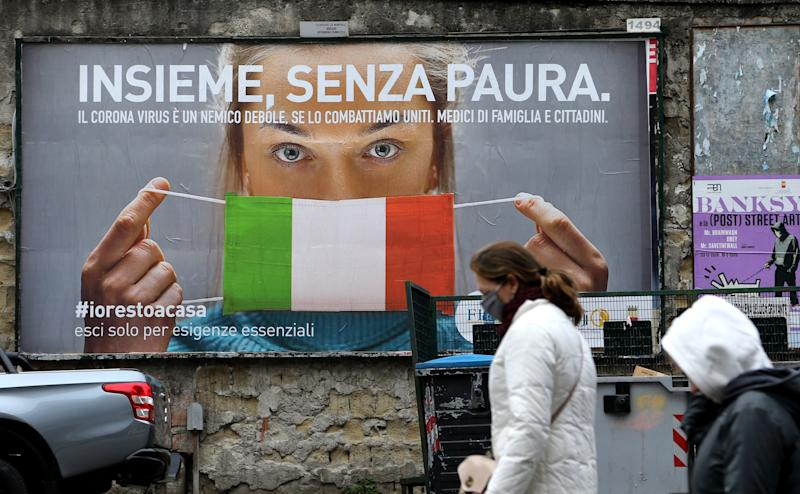 """People walk past a huge billboard that shows a woman with as protective mask in the colours of an Italian flag and which reads, """"All together, without fear"""" referring to the coronavirus campain to stay home in the city of Naples on March 22, 2020. - Italian Prime Minister Giuseppe Conte on March 21, 2020, ordered all non-essential companies and factories to close nationwide to stem a coronavirus pandemic that has killed 4,825 people in the country in a month. """"The decision taken by the government is to close down all productive activity throughout the territory that is not strictly necessary, crucial, indispensable, to guarantee us essential goods and services,"""" Conte said in a late-night TV address (Photo by Carlo Hermann / AFP) (Photo by CARLO HERMANN/AFP via Getty Images)"""