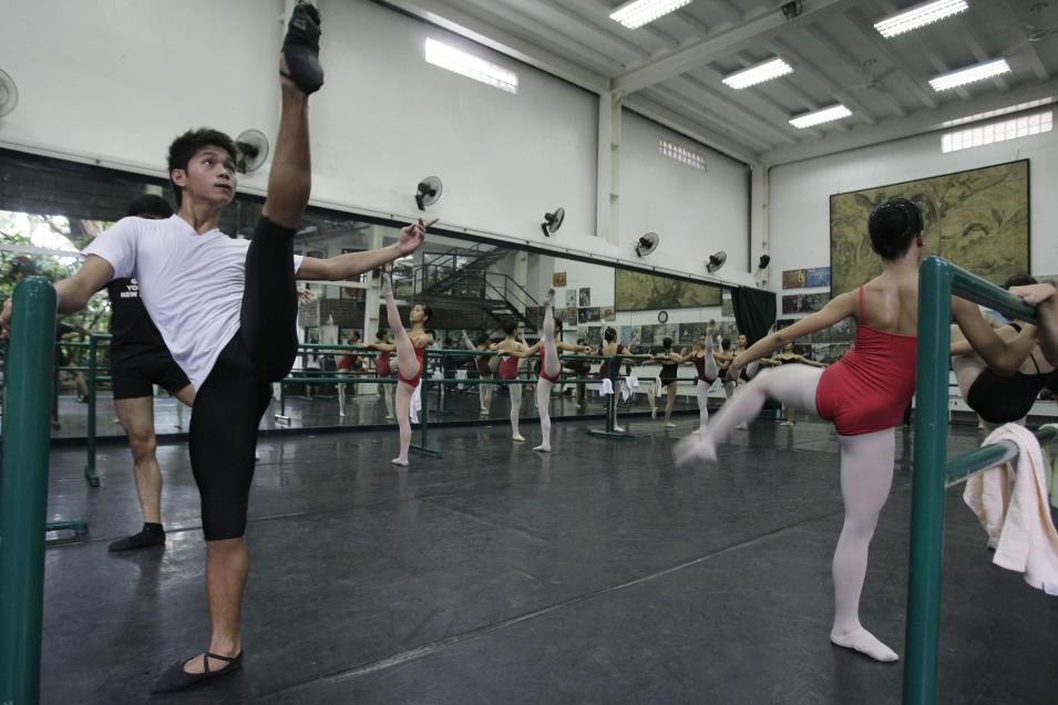 In this photo taken Nov. 25, 2012, Filipino slum dweller Jamil Montebon, left, practices steps during a class at Ballet Manila in the Philippine capital. Montebon, a scholar at Ballet Manila's program, used to collect garbage and also worked at a junk shop. He now receives a monthly stipend, stays at their dormitory and is given meals. (AP Photo/Aaron Favila)