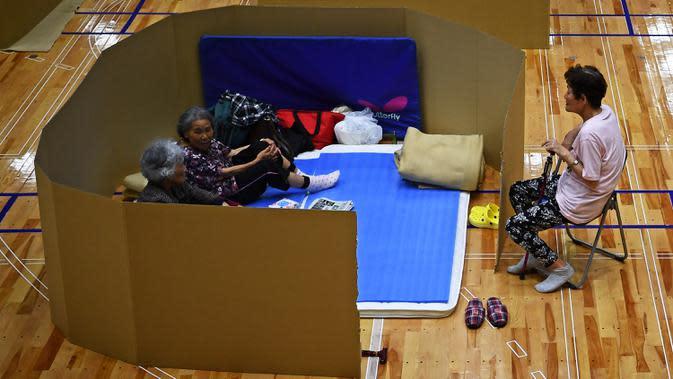 Penduduk setempat berbincang di pusat evakuasi dengan kotak kardus untuk menjaga jarak di sebuah gimnasium kota Yatsushiro di prefektur Kumamoto, Jepang, Senin (6/7/2020). Hujan deras menghambat operasi pencarian dan penyelamatan korban banjir dan tanah longsor di Kumamoto. (Charly TRIBALLEAU/AFP)