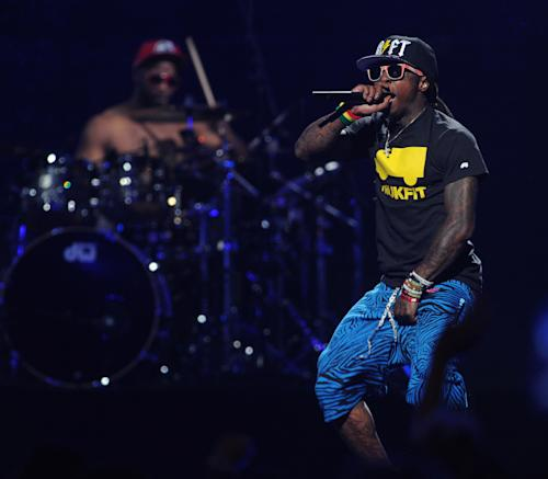 FILE - In this Sept. 21, 2012 file photo, Lil Wayne performs at the iHeart Radio Music Festival at the MGM Grand Arena in Las Vegas. Lil Wayne and Rick Ross, two of the most celebrated and successful artists in rap today, recently lost major endorsements after protests forced high profile corporations to drop the rap stars. Both artists rapped lyrics deemed vulgar and over-the-top; one referring to rape, the other about the beating of Emmett Till, on songs where they were the featured acts. (Photo by Eric Reed/Invision/AP, File)
