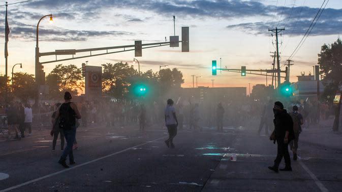 Demonstran bentrok dengan polisi saat unjuk rasa atas kematian George Floyd oleh polisi di luar Third Police Precinct, Minneapolis, Minnesota, Amerika Serikat, Rabu (27/5/2020). Pria kulit hitam, George Floyd, meninggal karena kehabisan napas setelah lehernya diduduki oleh polisi. (Kerem Yucel/AFP)