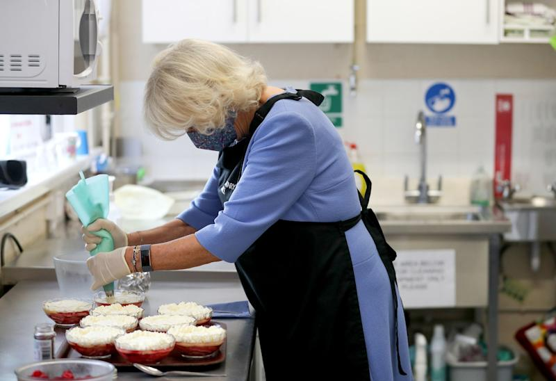 RICKMANSWORTH, ENGLAND - OCTOBER 08: Camilla, Duchess of Cornwall, in her role as President of the Royal Voluntary Service, works in the kitchen, piping cream onto a trifle dessert, during a visit to The Royal Voluntary Service Lunch Club on October 8, 2020 in Rickmansworth, England. (Photo by Andrew Matthews - WPA Pool/Getty Images)