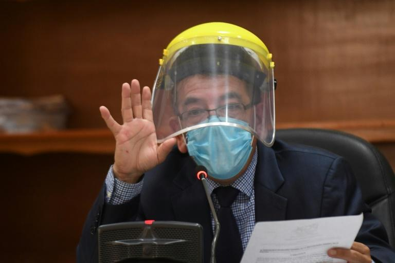 Judge Miguel Angel Galvez wears a face shield and a mask during a hearing against Guatemalan ex-president Otto Perez in Guatemala City on May 12, 2020