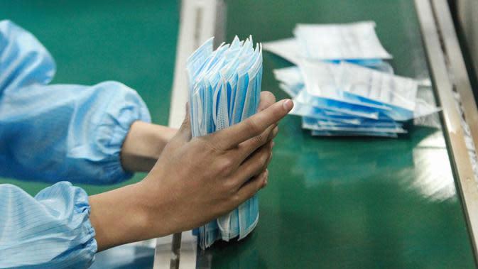 Pekerja memproduksi masker di sebuah pabrik di Yangzhou, Provinsi Jiangsu, China, Senin (27/1/2020). Masker tersebut diproduksi untuk mendukung pasokan bahan medis saat wabah virus corona melanda China. (STR/AFP)
