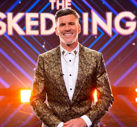The Masked Singer Australia host, Osher Günsberg wearing a gold jacket and white shirt in a promotional photo for the reality TV show. Photo: Channel 10.