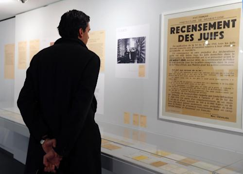 "A man looks at a poster reading ""Census of Jews"" displayed in an exhibition at the Shoah Memorial in Paris, Tuesday, Feb. 12, 2013. The French state prepares to give back seven stolen Nazi-era paintings - 4 of which are in the Louvre - to two Jewish families, after a decade-long tug of war. It ends years of struggle for the two families, whose claims were all validated by the French prime minister last year. (AP Photo/Jacques Brinon)"