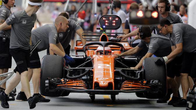 Kesibukan tim mekanik McLaren saat melihat kondisi mobil pebalap Stoffel Vandoorne di pit lane pada sesi latihan bebas F1 GP Singapura, Marina Bay City Circuit, (15/9/2017). (AP/Wong Maye-E)