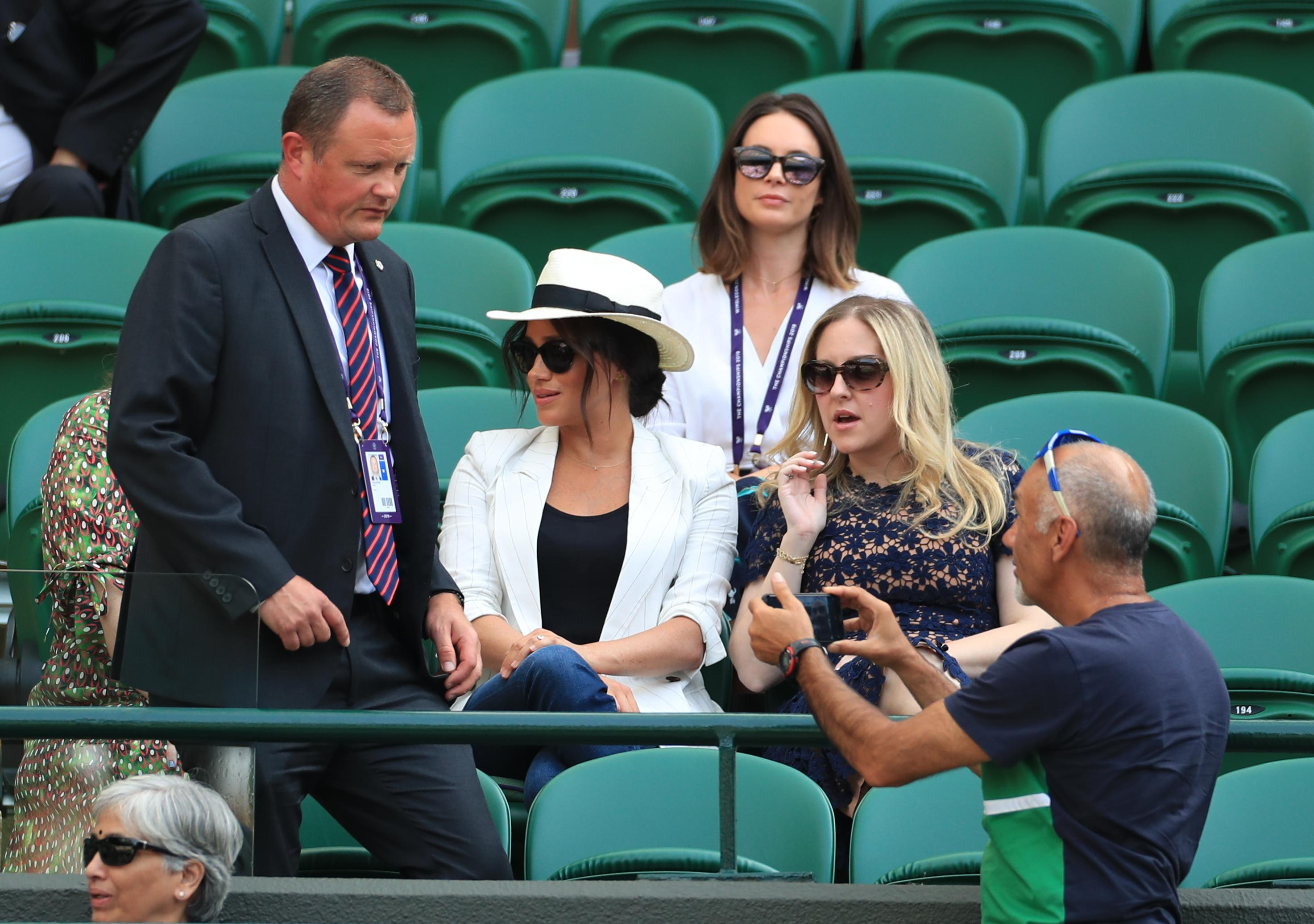 Previously unissued picture dated 4/7/2019 of a man believed to be a Royal bodyguard approaching a spectator who had taken a selfie as the Duchess of Sussex watches the Serena Williams match on court one during day four of the Wimbledon Championships at the All England Lawn Tennis and Croquet Club, Wimbledon. (Photo by Mike Egerton/PA Images via Getty Images)