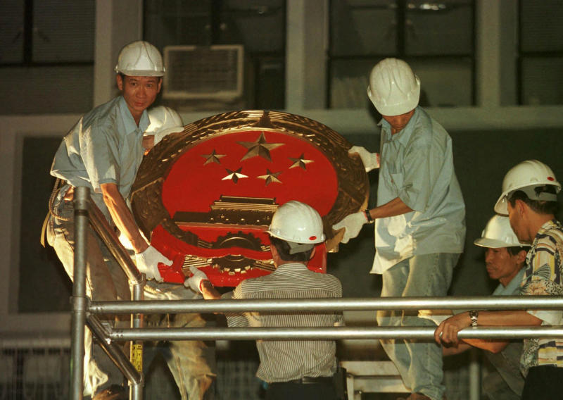 FILE - In this July 1, 1997, file photo, workers prepare to place a huge new Chinese governmental emblem on the wall of the Central Government Office in Hong Kong following the British handover of Hong Kong to China. Hong Kong has been living on borrowed time ever since the British made it a colony nearly 180 years ago, and all the more so after Beijing took control in 1997, granting it autonomous status. A national security law approved by China's legislature on May 28, 2020 is a reminder that the city's special status is in the hands of Communist Party leaders who have spent decades building their own trade and financial centers to take Hong Kong's place. (AP Photo/Dave Smith, File)