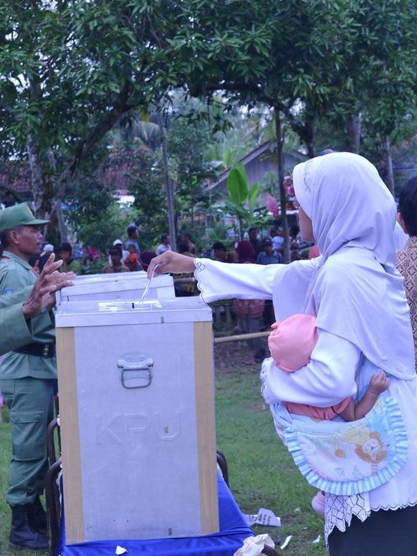 Seorang ibu menggendong bayinya untuk menunaikan hak pilihnya dalam Pilkades serentak Banyumas. (Foto: Liputan6.com/Muhamad Ridlo)