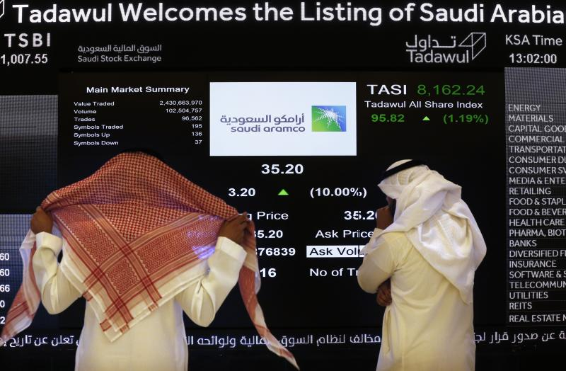 """FILE- In this Dec. 11, 2019, file photo, the Saudi stock market officials watch the stock market screen displaying Saudi Arabia's state-owned oil company Aramco after the debut of Aramco's initial public offering (IPO) on the Riyadh's stock market in Riyadh, Saudi Arabia. Saudi Arabian oil company Aramco's initial public offering raised $29.4 billion, more than previously announced after the company said Sunday it used a so-called """"greenshoe option"""" to sell an additional 450 million shares to satiate investor demand. (AP Photo/Amr Nabil)"""