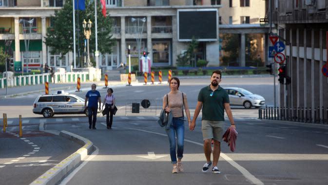 Warga berjalan di Victoriei Avenue, yang ditutup untuk kendaraan namun dibuka bagi pejalan kaki dan pesepeda pada akhir pekan, di Bucharest, Rumania, pada 7 Juni 2020. Setelah dua tahap penerapan langkah pelonggaran, warga Rumania kini menjalani
