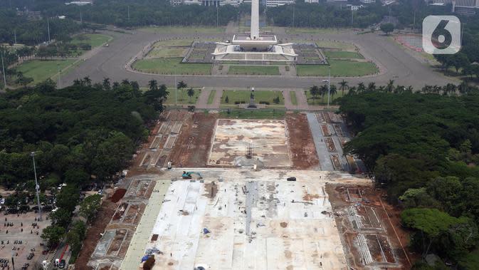 Aktivitas pengerjaan proyek revitalisasi Taman Sisi Selatan Monumen Nasional dilihat dari ketinggian, Jakarta, Minggu (19/1/2020). Proses revitalisasi dimulai dengan penebangan ratusan pohon di taman selatan Monas dan menjadikan kawasan tersebut terlihat gersang. (Liputan6.com/Helmi Fithriansyah)