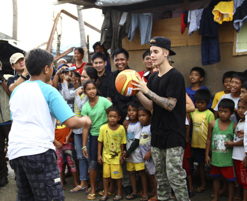 """Justin Bieber plays basketball with children survivors of Typhoon Haiyan during his unannounced visit Tuesday, Dec. 10, 2013 at Tacloban city, Leyte province in central Philippines. The teen heartthrob Bieber arrived Tuesday in the Philippines, where he has launched a campaign to help victims of last month's killer typhoon. Bieber, adored by young fans worldwide for hits like """"Baby,"""" arrived on a special flight, Immigration officer Jerome Ollet said. (AP Photo)"""