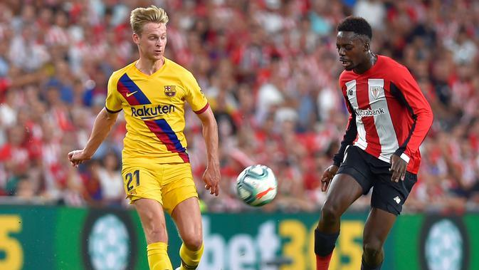 Striker Athletic Bilbao, Inaki Williams (kanan) membawa bola dari kejaran gelandang Barcelona, Frenkie de Jong selama pertandingan perdana La Liga Spanyol di Stadion San Mames, Sabtu (17/8/2019). Bilbao menang tipis atas Barcelona dengan skor 1-0. (AFP Photo/Ander Gillenea)