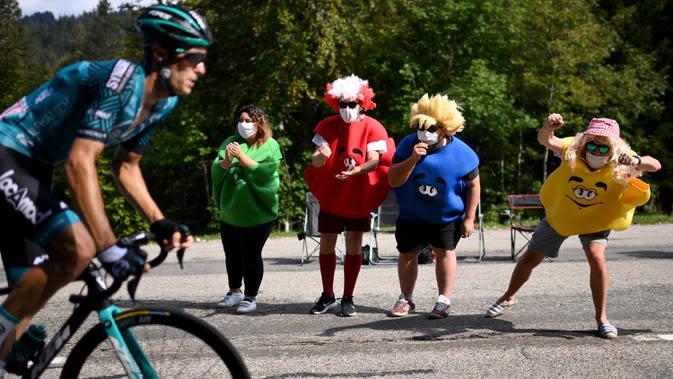Sejumlah penonton berkostum unik memberikan semangat kepada pebalap sepeda pada ajang balap sepeda Tour de France di La Tour du Pin, Selasa (15/9/2020). (AFP/Marco Bertorello)