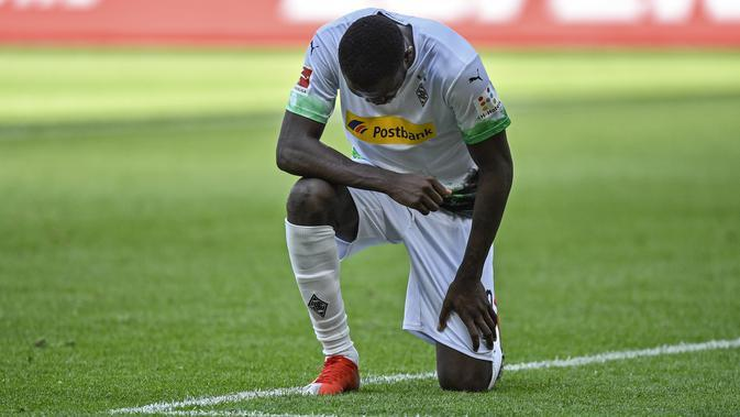 Penyerang Borussia Monchengladbach, Marcus Thuram, merayakan golnya ke gawang Union Berlin pada menit ke-41 dengan cara berlutut dan berdoa untuk George Flyod, Minggu (31/5/2020). (AFP/Martin Meissner / POOL)