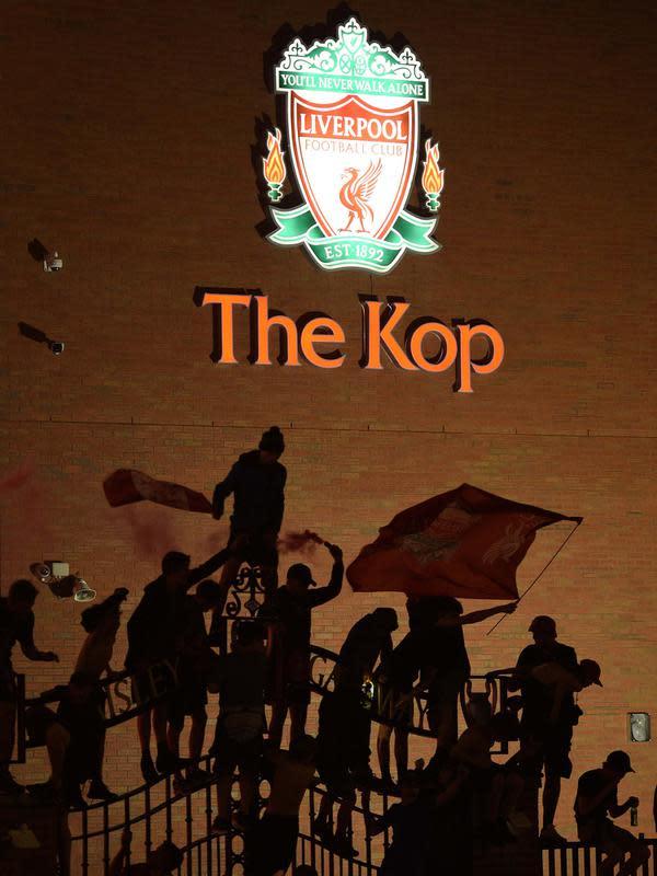 Para fans merayakan Liverpool memenangkan gelar juara Liga Primer Inggris di luar stadion Anfield di Liverpoo (25/6/2020). Liverpool meraih mahkota juara Liga Premier Inggris setelah mengakhiri gelar selama 30 tahun penantian. (AFP Photo/Oli Scarff)