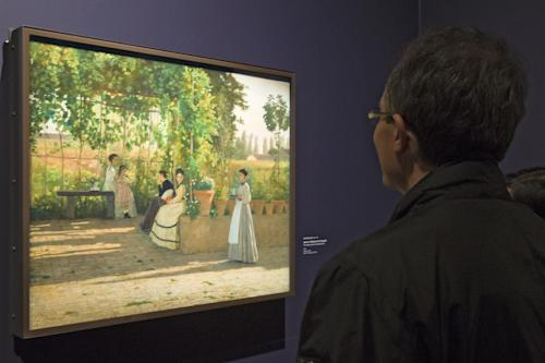 """A visitors looks at the painting ''After Lunch"""" (La Pergola),1868, by Silvestro Lega, at the Orangerie Museum in Paris, Tuesday April 9, 2013. A new exhibit at Paris' Orangery museum called """"The Macchiaioli: the Italian Impressionists?"""" explores how a Florence-based art movement that predated French impressionism by a decade was already using the themes of light, the outdoors and spontaneity that's more associated with the likes of Monet or Renoir. (AP Photo/Jacques Brinon)"""