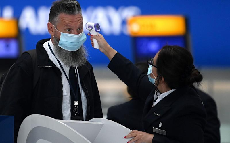 Passengers wearing face masks or coverings due to the COVID-19 pandemic, have their temperature taken as they queue at a British Airways check-in desk at Heathrow airport - DANIEL LEAL-OLIVAS/AFP