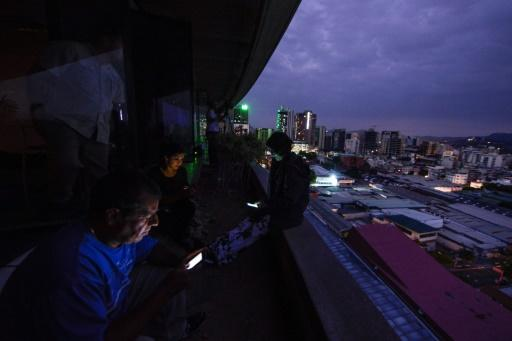 Journalists use cell phones during a huge blackout in Venezuela