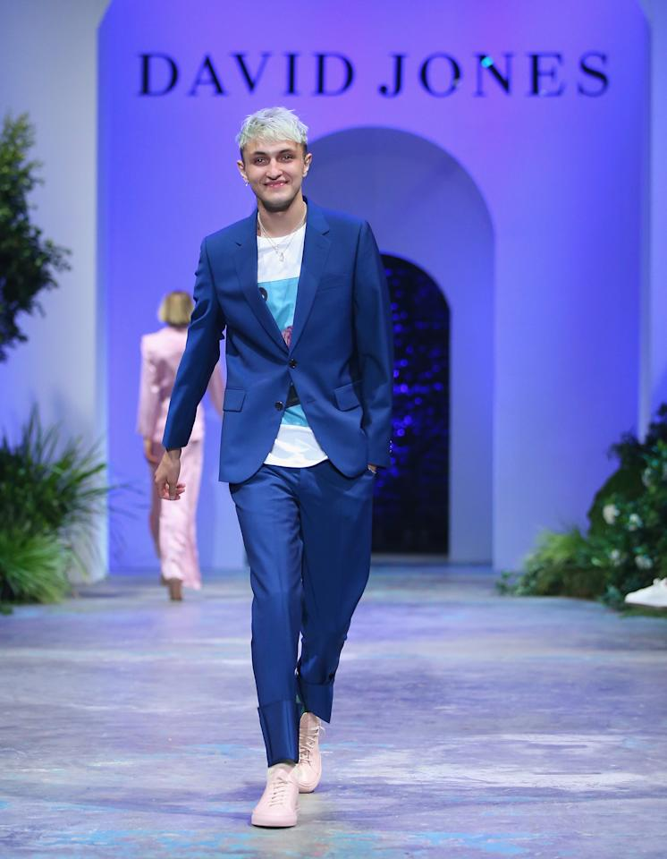 <p>Anwar Hadid couldn't resis a cheeky smile as he emerged onto the catwalk looking dapper in a blue suit, white logo tshirt and a pair of cool pink runners. Photo: Getty Images </p>