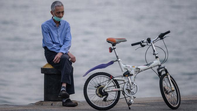 Seorang pria mengenakan masker beristirahat di samping sepedanya di tambatan di kargo yang dijuluki 'Instagram Pier' di Hong Kong (21/4/2020). Hong Kong melaporkan penurunan kasus infeksi harian Covid-19, tetapi pemerintah kota mengatakan mereka tidak mengambil risiko apa pun. (AFP/Anthony Wallace)