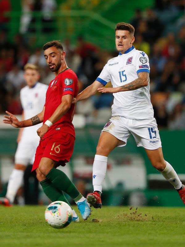 Gelandang timnas Portugal Bruno Fernandes berebut bola dengan pemain timnas Luksemburg, Olivier Thill dalam laga lanjutan Grup B Kualifikasi Piala Eropa 2020 di Estadio Jose Alvalade, Jumat (11/10/2019). Portugal meraih kemenangan 3-0 atas tamunya, Luksemburg. (AP/Armando Franca)