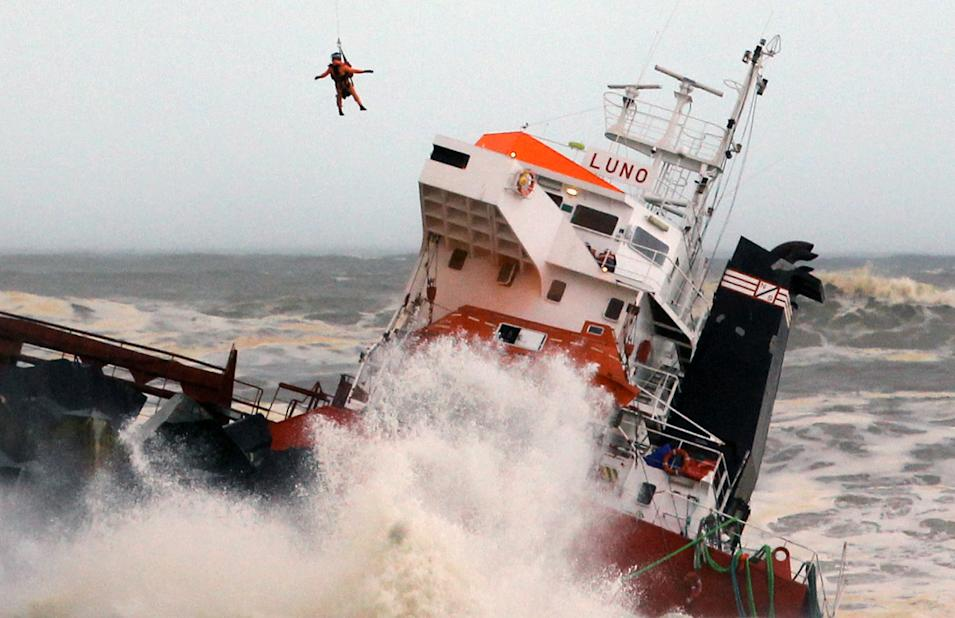 A helicopter lowers a rescue worker toward a Spanish cargo ship the Luno that slammed into a jetty in choppy Atlantic Ocean waters off Anglet, southwestern France, Wednesday Feb. 5, 2014. The ship had been heading to a nearby port to load up with cargo when its engine failed and the rough waves carried it into the jetty. (AP Photo/Bob Edme)