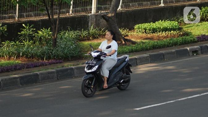 Pengendara motor tanpa mengenakan masker melintas di Kawasan Jakarta, Selasa (19/5/2020). Sanksi PSBB yang kurang tegas menyebabkan sebagian warga masih bebas beraktivitas tanpa menggunakan masker, meskipun resiko penyebaran virus corona masih tinggi. (Liputan6.com/Immanuel Antonius)