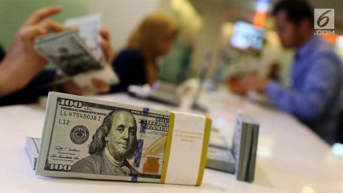 Petugas bank menghitung uang dollar AS di Jakarta, Jumat (20/10). Nilai tukar Rupiah terhadap Dolar Amerika Serikat (USD) masih belum beranjak dari level Rp 13.500-an per USD. (Liputan6.com/Angga Yuniar)