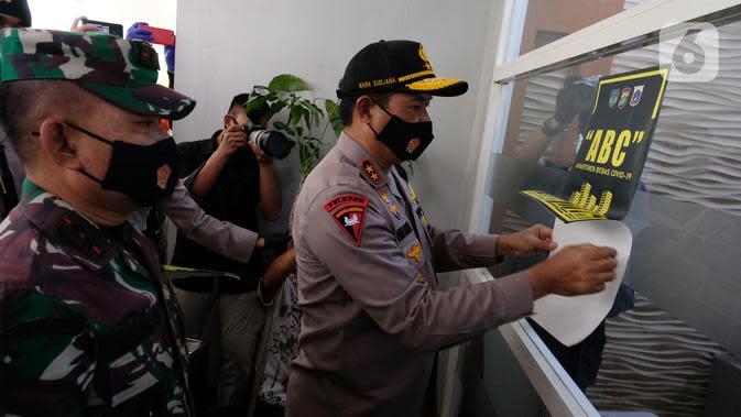 Kapolda Metro Jaya Irjen Nana Sujana dan Pangdam Jaya Mayjen TNI Dudung Abdurachman menempel stiker Apartemen Bebas Covid-19 (ABC) di Jakarta, Kamis (1/10/2020). Program ABC yang diinisiasi oleh Kepolisian Resor bertujuan untuk menerapkan kedisiplinan protokol kesehatan. (Liputan6.com/Fery Pradolo)