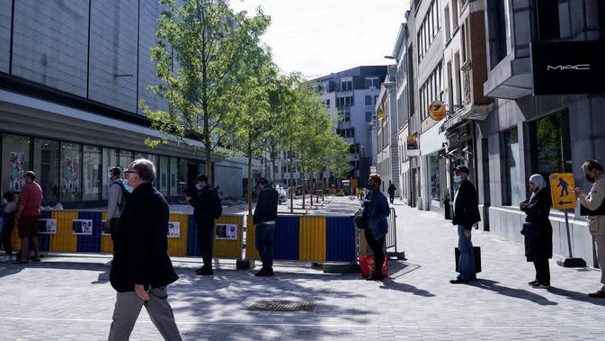 Pelanggan antre memasuki toko pakaian pada hari pembukaannya kembali setelah pelonggaran lockdown di Brussel, Senin (11/5/2020). Warga Belgia rela menghabiskan waktu selama berjam-jam sebelum toko dibuka untuk berbelanja pertama kalinya sejak lockdown pada Maret lalu (Kenzo TRIBOUILLARD/AFP)