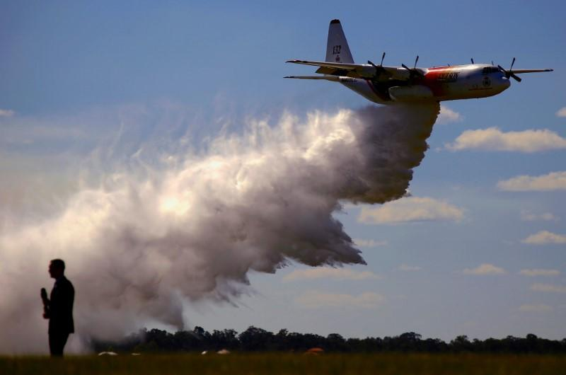 FILE PHOTO: A television reporter stands in front of the Large Air Tanker C-130 Hercules, also known as 'Thor', as it drops a load of around 15,000 litres during a display by the Rural Fire Service ahead of the bushfire season at RAAF Base Richmond in