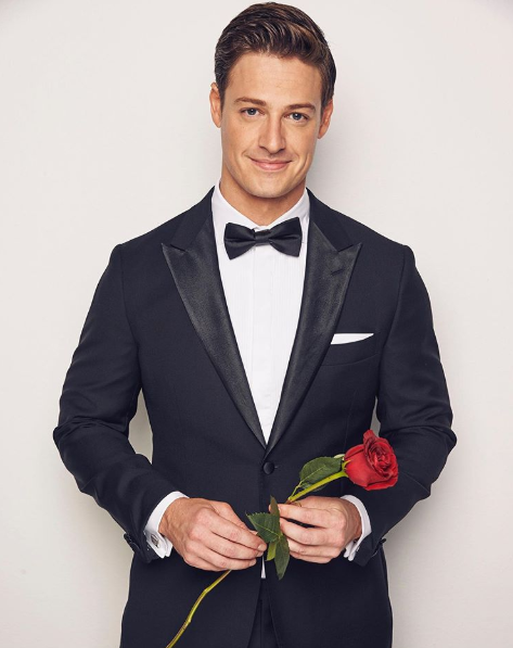 A photo of The Bachelor Australia Matt Agnew wearing a tuxedo and holding a red rose.