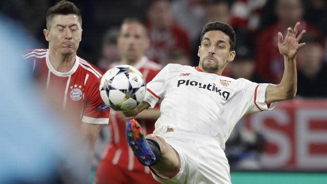 Pemain Bayern, Robert Lewandowski (kiri) berebut bola dengan pemain Sevilla, Jesus Navas pada leg kedua perempat final Liga Champions di Allianz Arena stadium, Munich, (11/4/2018). Bayern lolos ke semifinal dengan agregat 2-1. (AP/Matthias Schrader)